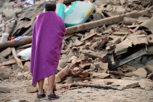 Un uomo davanti alle macerie di una casa distrutta dal terremoto ad Amatrice, 24 agosto 2016 (FILIPPO MONTEFORTE/AFP/Getty Images)